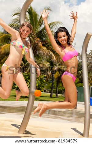 Pretty young blond and brunette women enjoying South Pointe Park in Miami Beach. - stock photo