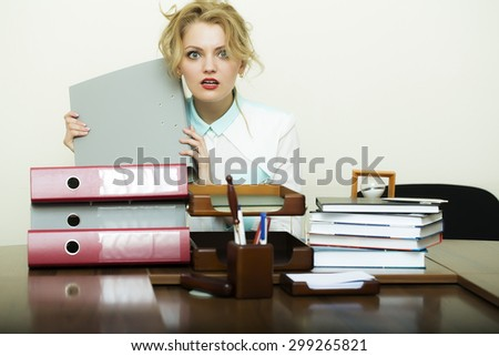 Pretty young blond business woman sitting in office at table with many documents files has a lot of work holding grey folder in hands on white background, horizontal picture - stock photo
