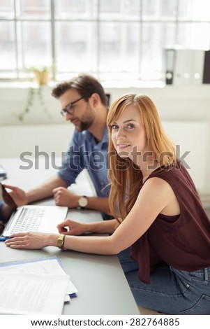 Pretty Young Blond Businesswoman Sitting at the Table with Laptop Beside her Male Partner, and Looking at the Camera. - stock photo