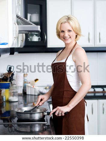 Pretty young blond woman cooks dinner in her kitchen - stock photo