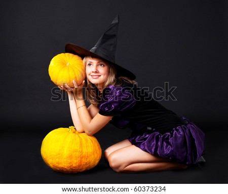 pretty young blond woman dressed as a fairy with pumpkins