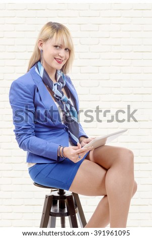 pretty young blond woman in blue suit, with tablet, sitting on a stool