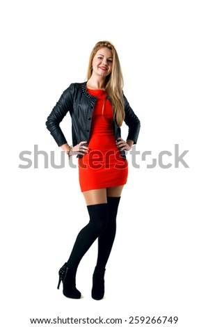 Pretty young blond woman model in tight short red dress, black leather jacket, stockings, high heel shoes, standing, posing, smiling with toothy smile, looking at camera. Isolated over white - stock photo