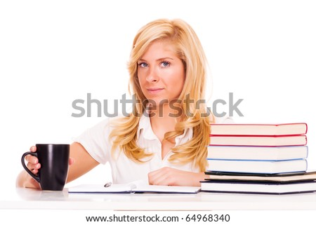 Pretty young blond woman sitting at the desk with books drinking coffee from the mug