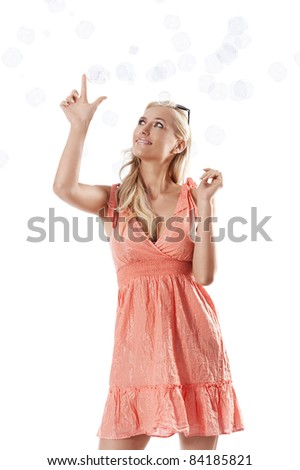 pretty young blond woman wearing a summer orange dress standing against white background playing with some soap bubbles - stock photo