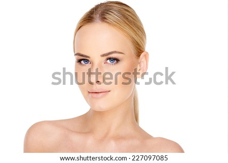 Pretty young blond woman with blue eyes and her long hair tied back in a ponytail looking at the camera with a serious expression  head and bare shoulders on white