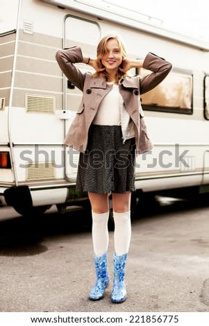 Pretty young blonde fashion sensual smiling woman posing in autumn outdoor on the street urban background after the rain in rubber shoes  - stock photo