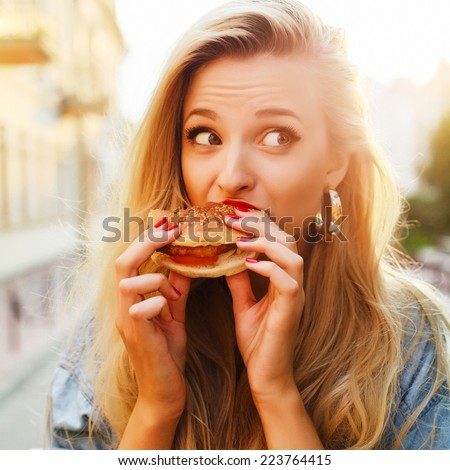 Pretty young blonde funny woman eating hamburger outdoor on the street  - stock photo