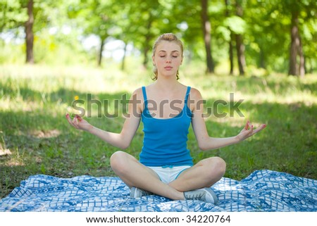 Pretty young blonde girl doing aerobics or yoga outdoor, in the forest