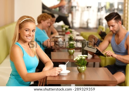 Pretty young blonde girl having coffee-break in gym. - stock photo