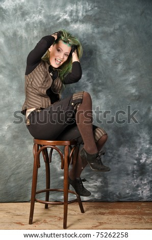 Pretty young blonde girl with green hair in the steampunk style demonstrates the fear - stock photo