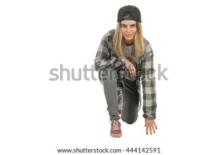 Pretty young blonde girl with ring in her nose in casual clothes standing on one knee in studio on white background isolated
