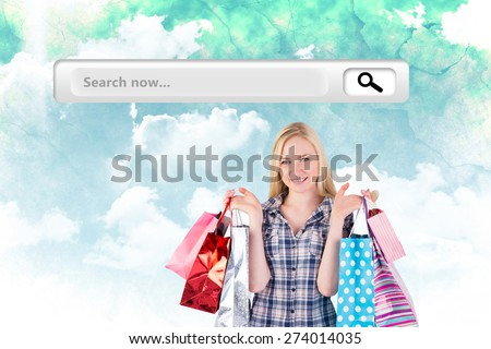 Pretty young blonde holding shopping bags against green and blue sky - stock photo