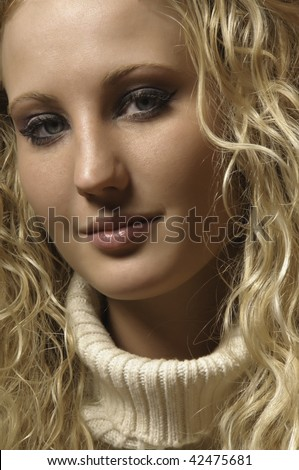 Pretty young blonde in light turtleneck with Mona Lisa smile