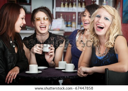 Pretty young blonde laughing with three friends in a cafe - stock photo