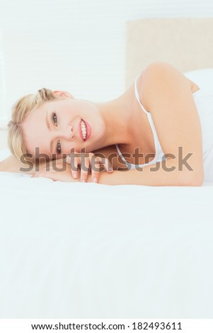 Pretty young blonde lying on her bed smiling at camera at home in the bedroom
