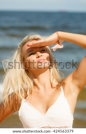 Pretty young blonde pretty girl at beach covering eyes. Woman have active time in summer. Summertime carefree concept. - stock photo