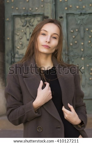 Pretty young  blonde woman in a grey coat at the street - stock photo