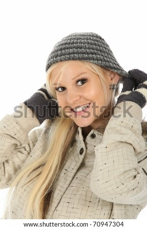 Pretty young blonde woman putting on a knitted woolen hat - stock photo