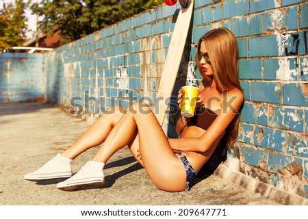 Pretty young blonde woman sitting near the beach with longboard and cocktail in summer in hot sexy bikini and have fun alone brazil style - stock photo