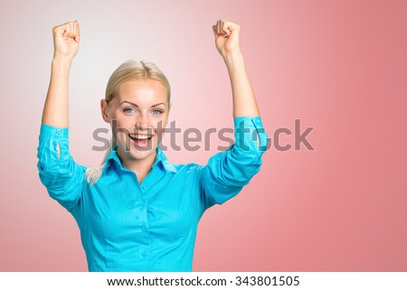 Pretty young blonde woman throwing her arms up into the air and laughing in jubilation at her success or victory