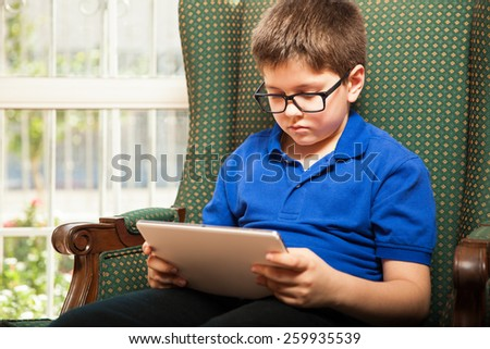 Pretty young boy with glasses watching a movie on a tablet computer at home - stock photo