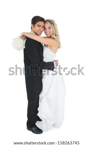 Pretty young bride holding a white bouquet embracing her husband - stock photo