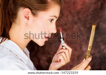 Pretty young brunette applying lipstick while looking at the mirror - stock photo