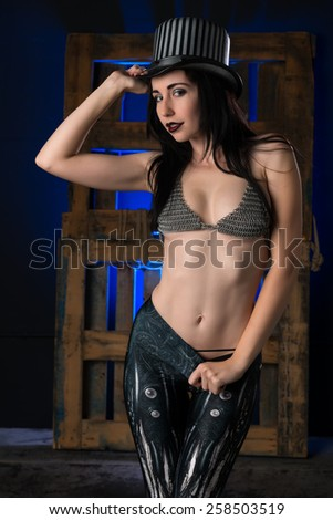 Pretty young brunette dressed in goth gear - stock photo
