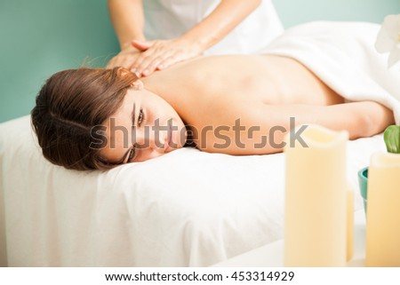 Pretty young brunette getting a back rub at a health spa and looking very relaxed - stock photo