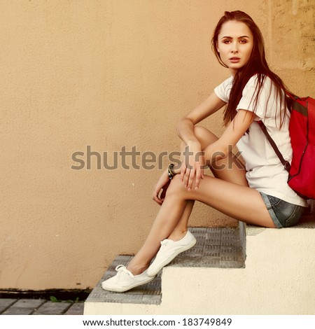 Pretty young brunette hipster woman posing outdoor in summer with red backpack traveling style. Beautiful girl sitting and having fun outdoor near yellow wall