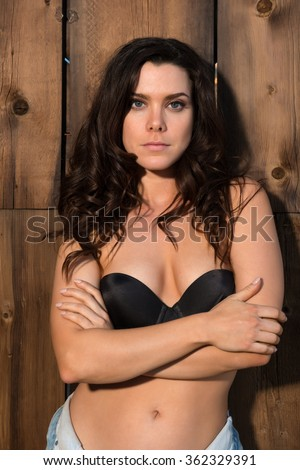 Pretty young brunette in a black bra and denim shorts - stock photo