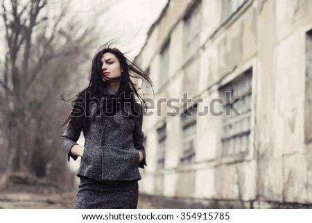 Pretty young brunette long haired woman in grey outfit posing outdoor in cold spring windy weather  - stock photo
