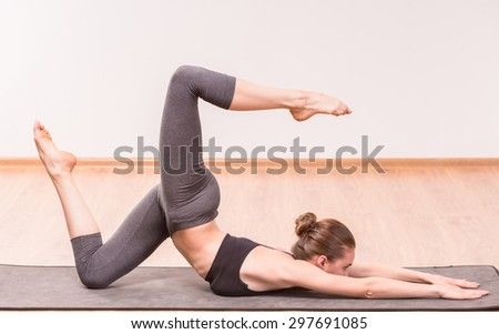 Pretty young brunette practicing yoga on mat.