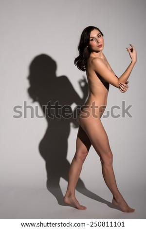 Pretty young brunette standing nude with her shadow - stock photo