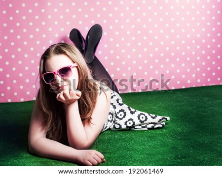 Pretty young brunette teenager girl lying on grass, wearing sunglasses, relaxing. - stock photo