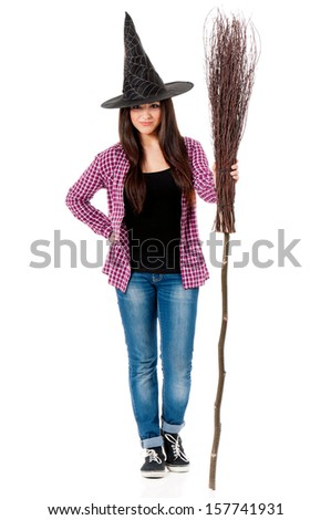 Pretty young brunette witch with a broom, isolated on white background  - stock photo