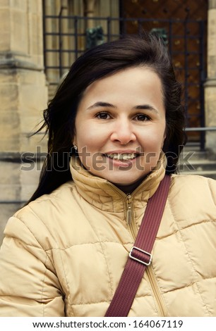 Pretty young brunette with charming smile on old town background - stock photo