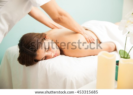 Pretty young brunette with eyes closed getting a massage and relaxing at a health clinic - stock photo