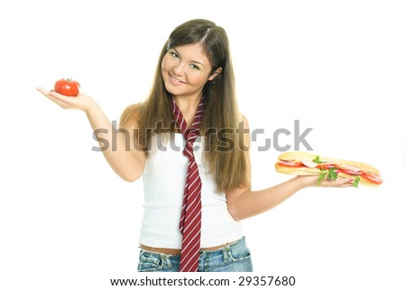 pretty young brunette woman choosing between a sandwich and a tomato - stock photo