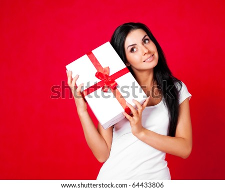 pretty young brunette woman dressed in red dress with a present - stock photo