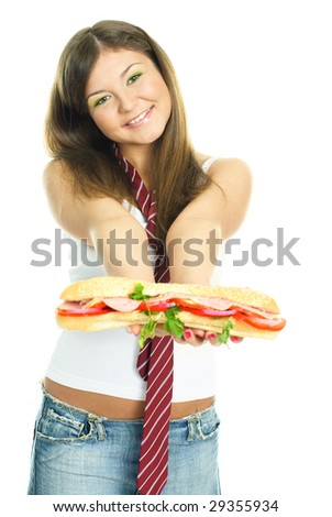 pretty young brunette woman giving us a huge sandwich with a smile - stock photo