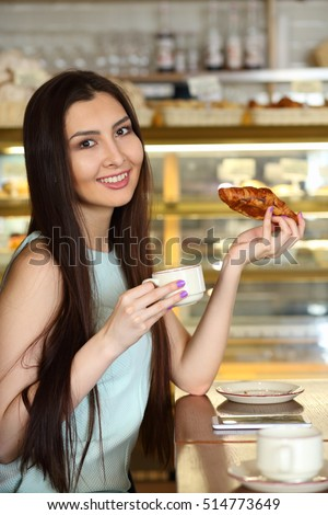 Pretty young brunette woman holds cup of tea and croissant in cafe and looks at camera