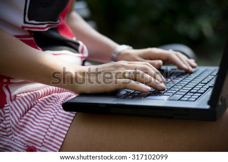 Pretty young brunette woman in park using new technology devices while relaxing on a beautiful day - stock photo