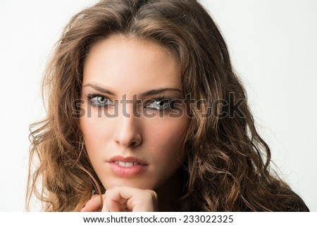 Pretty young brunette woman in 20s with curly hair, isolated against white.