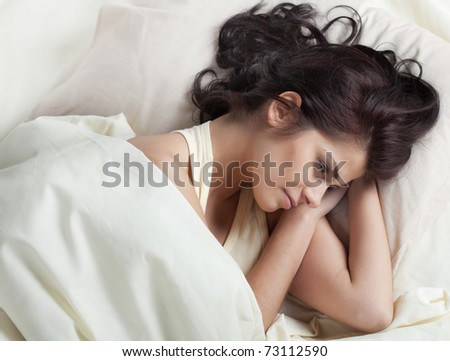 Pretty young brunette woman lying in bed