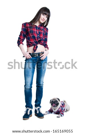 Pretty young brunette woman model with long straight hair standing together with her friend pug dog pet, both wearing squared pattern shirts girl wearing jeans and cool winter shoes. Isolated on white - stock photo