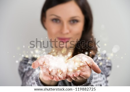 Pretty young brunette woman smiling against gray background with magic sparkle in her hands cupped together - stock photo