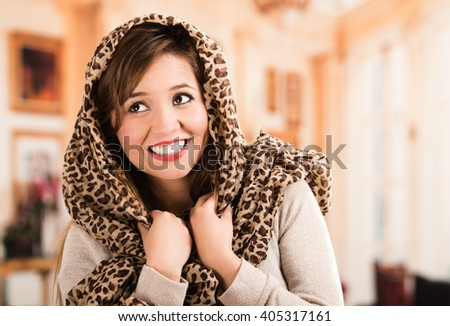 Pretty young brunette woman wearing beige sweater and covering head with brown scarf smiling. - stock photo