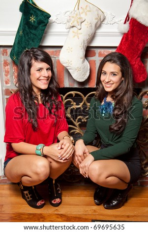 Pretty young brunette women in a holiday lifestyle home setting with fireplace and holiday stockings.